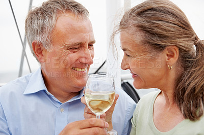 Buy stock photo Closeup of a senior couple celebrating with a champagne on a boat voyage