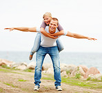 Happy woman being carried on a man's back, hands outstretched