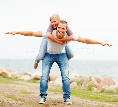 Buy stock photo Young couple enjoying themselves out in the open, female on man's back