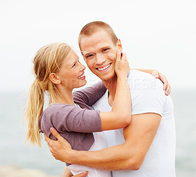 Buy stock photo Young couple enjoying themselves outdoors, embracing