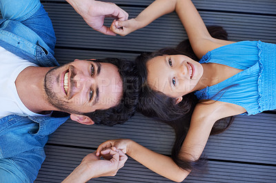 Buy stock photo High angle portrait of a father and daughter lying on the floor and holding hands