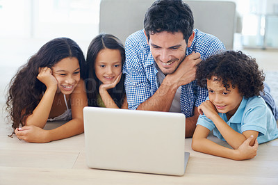 Buy stock photo Shot of a family lying on the floor and surfing the internet
