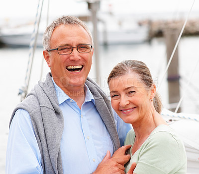 Buy stock photo Portrait of a retired couple embracing on sailboat, laughing