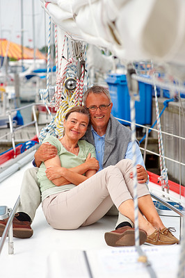 Buy stock photo Happy mature woman sitting comfortably with her husband on a sailboat