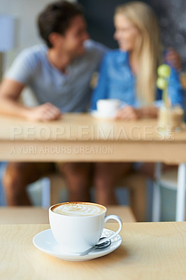 Buy stock photo A cappuccino on a coffee shop table with a young couple blurred in the background