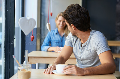 Buy stock photo A young man in a coffee shop looking over his shoulder to see the girl behind him