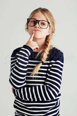 Buy stock photo A cute girl looking thoughtful with her finger to her mouth
