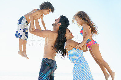 Buy stock photo A young couple raising their children up in the air while standing back to back