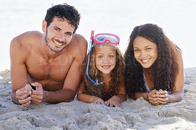 Buy stock photo A happy couple lying on the beach with their sweet little daughter between them - portrait