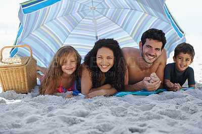 Buy stock photo A happy family smiling at the camera while lying under an umbrella at the beach