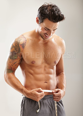 Buy stock photo A hunky young man measuring his stomach