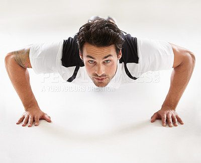 Buy stock photo Portrait of a young man doing push-ups