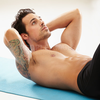 Buy stock photo A handsome young man doing crunches without a shirt