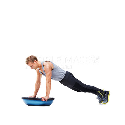 Buy stock photo An athletic young man using a bosu-ball for an upper body workout