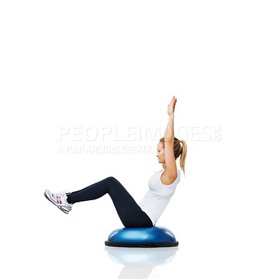 Buy stock photo An attractive young woman balancing on a bosu-ball while working out