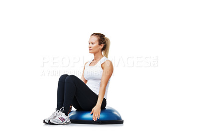 Buy stock photo A young woman sitting on a bosu-ball while exercising