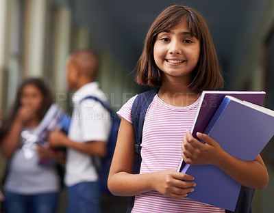 Buy stock photo Portrait of a happy school girl standing in the corridor with her friends in the background