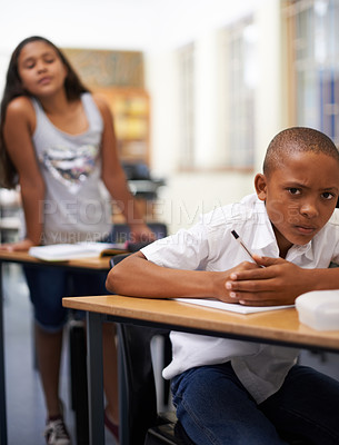 Buy stock photo Portrait of a young boy writing a test while a classmate tries to copy