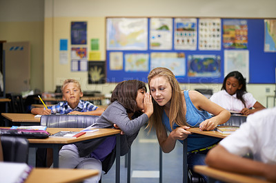 Buy stock photo A teenage girl whispering in her friends ear int he middle of a classroom