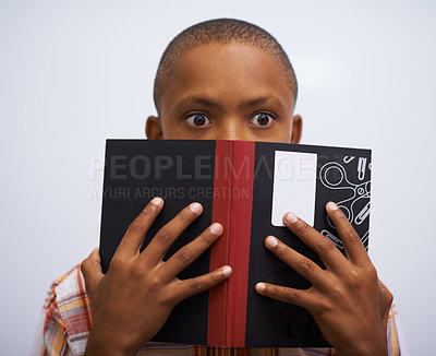 Buy stock photo A young boy peering out from behind his book and looking nervous