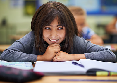 Buy stock photo A young girl working on her schoolwork in class