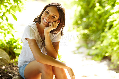 Buy stock photo Portrait of sweet young woman sitting outdoors and smiling