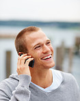 Smart happy guy speaking on his cellphone outdoors