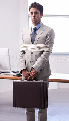 Buy stock photo A young businessman tied up at the office