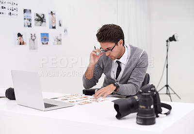 Buy stock photo Shot of a young photographer sitting at his desk editing images