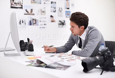 Buy stock photo A photographer looking at his images in his office