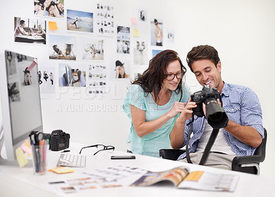 Buy stock photo A photographer looking at his images in his office with his assistant