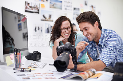 Buy stock photo Two young photographers looking at photos on a digital camera in their studio