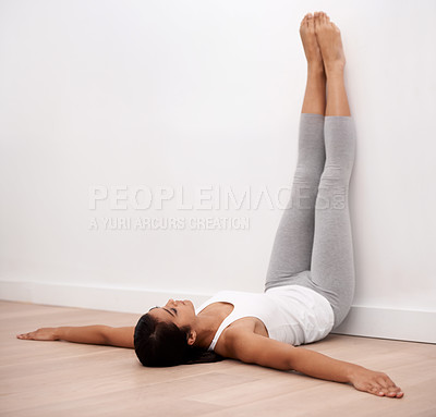 Buy stock photo A young woman stretching against a wall before exercise
