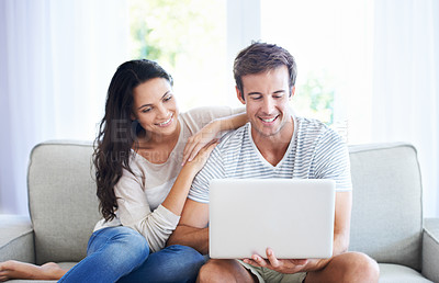 Buy stock photo A young couple relaxing on the couch using a laptop