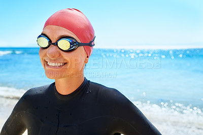 Buy stock photo A young woman training in a full piece wetsuit and swimming gear on the beach in the winter
