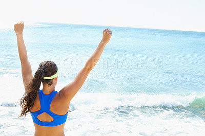 Buy stock photo Rearview shot of a young woman looking out over the sea with her arms raised in celebration