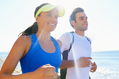 Buy stock photo A young couple running together at the coast