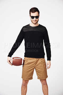 Buy stock photo A confident young man looking stylish while holding a football