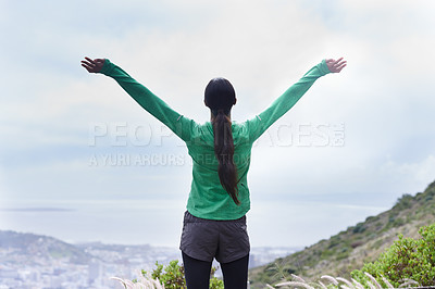 Buy stock photo Rearview of an adventurous young woman standing with her arms outstretched on the mountain