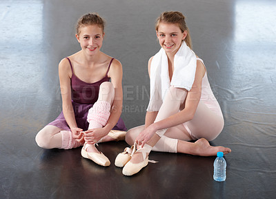 Buy stock photo Two young ballerinas tying their ballet slippers in a dance studio