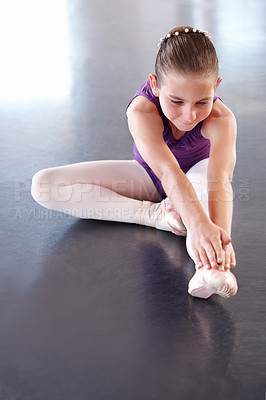 Buy stock photo A young ballerina tying her ballet slipper