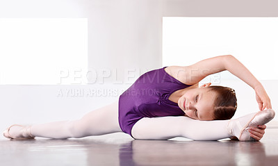 Buy stock photo A young ballerina stretching on the floor