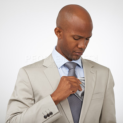 Buy stock photo A stylish young african-american man straightening his tie