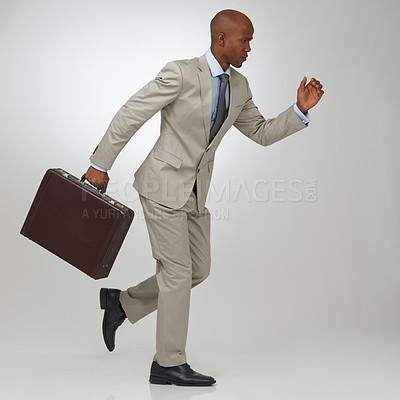 Buy stock photo An African-American businessman running with his briefcase