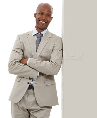 Buy stock photo A handsome African-American businessman leaning against a wall