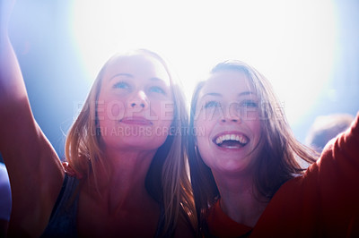 Buy stock photo Two young female fans cheering at a rock concert. This concert was created for the sole purpose of this photo shoot, featuring 300 models and 3 live bands. All people in this shoot are model released.