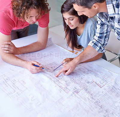 Buy stock photo Three architects working on their blueprints together in the boardroom