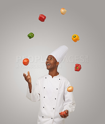 Buy stock photo A young African-American chef juggling with vegetables