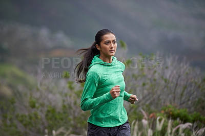 Buy stock photo Shot of a beautiful young woman exercising in the mountains