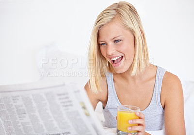 Buy stock photo A pretty young woman reading the newspaper in bed and enjoying a glass of OJ